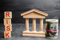 Dollars, government building and inscription `Risk` on wooden blocks.The risk of investing in a business project. Short-term inves stock photography
