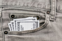 Dollars in grey jean pocket Stock Photography