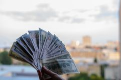 Dollars in hand against the backdrop of a big city. stock photo