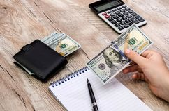 Dollars in hand, calculator, notepad and pen on a wooden background royalty free stock photography