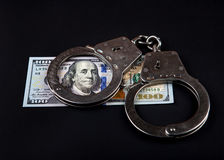 Dollars and Handcuffs. American Dollars and Handcuffs on the Black Background Royalty Free Stock Photo