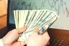 Dollars in handen op computerachtergrond, het concept het kopen op Internet, investering, succes, het gokken Internet-fraude, bee stock afbeeldingen