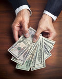 Dollars Hands Business Money. A business man holding a large quantity of American money in his hands on a wood desk surface Stock Photo