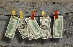 Dollars hang on a rope. Against a concrete wall Royalty Free Stock Photos
