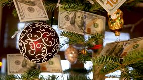 Christmas tree with dollars. The dollars are hanging on the Christmas tree stock video footage
