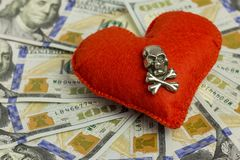 Dollars, heart, death. Concept Wedding contract, dangerous love for money, terrible Valentine`s Day. Piracy and feelings. Close-u Royalty Free Stock Photography
