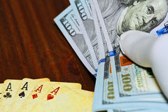 Dollars holded in hand over the poker playing cards Royalty Free Stock Images