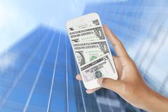 Dollars inside smartphone with abstract blurred motion of modern glass building.  Royalty Free Stock Image