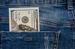 Dollars in jeans pocket. Dollars that look out of jeans pockets royalty free stock photos