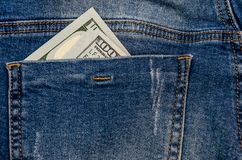 Dollars in jeans pocket. Dollars that look out of jeans pockets stock image