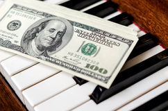 Dollars on keyboard of piano Royalty Free Stock Photo