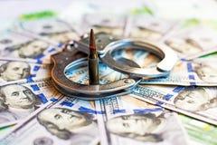 Dollars, kogel en handcuffs als abstract symbool van terrorisme, financiële criminaliteiten en corruptie van ambtenaren en politi royalty-vrije stock foto's