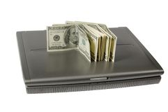 Dollars and the laptop. Some hundred dollar denominations lie on the laptop Royalty Free Stock Photo