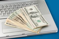 Dollars on a laptop Stock Images