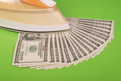 Dollars lay under an electric iron Royalty Free Stock Images