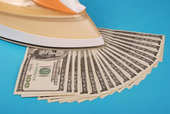 Dollars lay under an electric iron Royalty Free Stock Photo