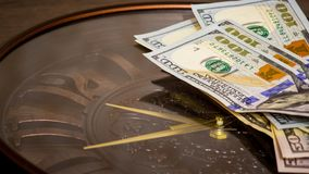 Dollars lie on the big clock. Time to sum up in financial matters.Time to earn money. Time is money_. Dollars lie on the big clock. Time to sum up in financial stock photo