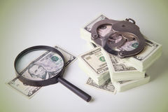 Dollars, magnifier and handcuffs Royalty Free Stock Photos