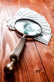 Dollars and magnifying glass. Fan of one hundred dollars banknotes lying on wooden table with vintage magnifying glass Stock Photography