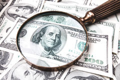 Dollars and magnifying glass Stock Images