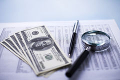 Dollars with a magnifying glass, pen and report Stock Photos