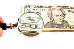 Dollars and magnifying glass Stock Image