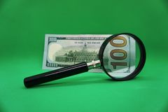 100 dollars and magnifying loupe stock image