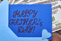 Dollars near Father`s Day card. Royalty Free Stock Image