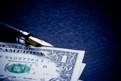 Dollars near golden fountain pen on old wood Royalty Free Stock Photos