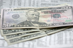 Dollars and newspaper Stock Photo