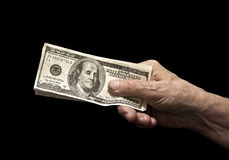 Dollars in old hand. On black background Royalty Free Stock Photo