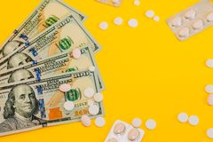Dollars and pills on yellow background close up royalty free stock images