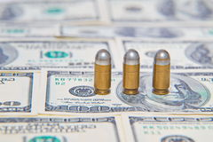Dollars and and pistol bullet. Background Stock Image