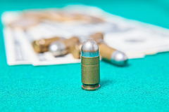 Dollars and pistol bullet. On a green cloth Stock Photos