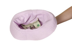 Dollars placed on cap which is held by man Royalty Free Stock Photography