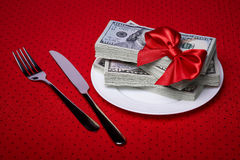 Dollars on a plate and cutlery Stock Image