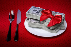 Dollars on a plate and cutlery Stock Images