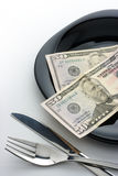 Dollars on plate with fork and knife Stock Photos