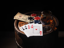 Dollars and playing cards on a wooden barrel Stock Photos