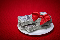 Dollars on a red tablecloth. Bundle of dollars on a plate, paper money, red bow of the braid, economic concept, serving business lunch, a red tablecloth in a Stock Image