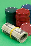 Dollars rolled into tube and gambling chips Royalty Free Stock Photo