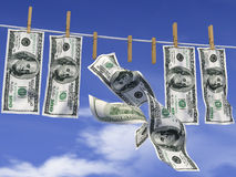Dollars on a rope. Dollars with clothespins hanging on a rope on the background of sky Stock Photo