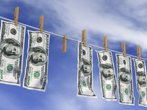 Dollars on a rope. Dollars with clothespins hanging on a rope on the background of sky Royalty Free Stock Photo