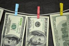 100 dollars sèchent sur la corde à linge Photographie stock