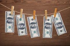 Dollars s'arrêtant sur la corde avec des pinces à linge Photographie stock libre de droits