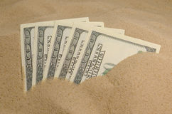 Dollars in sand Stock Image