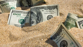 Dollars in sand on a beach. One hundred dollars in sand on a beach Royalty Free Stock Image