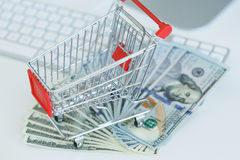 Dollars and shopping cart on a computer keyboard Royalty Free Stock Photos