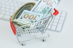 Dollars in the shopping cart on a computer keyboard Royalty Free Stock Photos