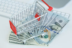 Dollars and shopping cart on a computer keyboard Stock Images
